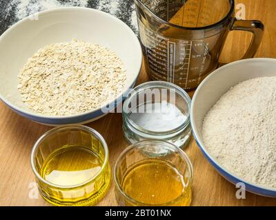 Ingredients for oat and spelt soda bread laid out on a kitchen table - Stock Photo