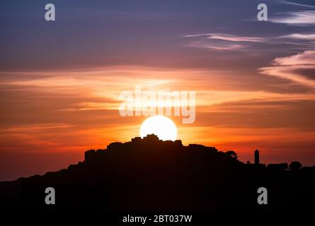 Orange and purple glow as the sun sets behind the silhouetted remote mountain village of Sant'Antonino in the Balagne region of Corsica - Stock Photo