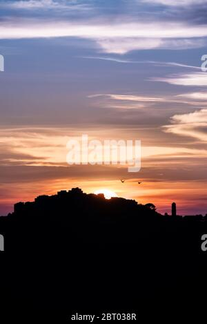 Two birds flying past the orange and purple glow as the sun sets behind the silhouetted remote mountain village of Sant'Antonino in the Balagne region - Stock Photo