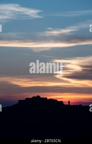 Orange and purple afterglow as the sun sets behind the silhouetted remote mountain village of Sant'Antonino in the Balagne region of Corsica - Stock Photo