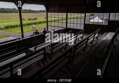Dresden, Germany. 22nd May, 2020. Horse racing: Gallop, special race day at the Dresden racetrack. The jockeys ride in front of the almost deserted grandstand on the home stretch during a 1500 meter race. Since the Halle race club has been banned from holding any kind of competition until 27 May by the current Corona regulation in Saxony-Anhalt, the race day on 22 May in Halle will be cancelled. Dresden is stepping in with a special race day. Credit: Robert Michael/dpa-Zentralbild/dpa/Alamy Live News - Stock Photo