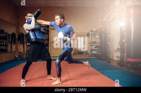 Male kickboxer in gloves practicing hand punch with a personal trainer in pads, workout in gym. Boxer on training, kickboxing practice - Stock Photo