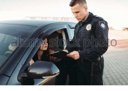 Male cop in uniform checks license of female driver. Law protection, car traffic inspector, safety control job - Stock Photo