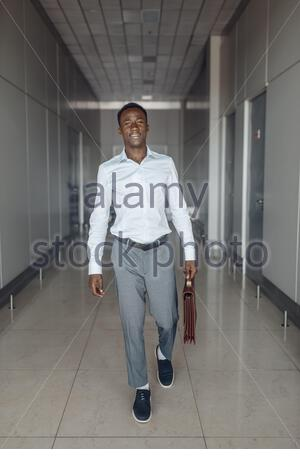 Ebony businessman with briefcase in office hall. Successful business person walking down the corridor, black man in formal wear - Stock Photo