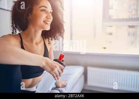 Fit girl in sportswear sitting on the sofa - Stock Photo