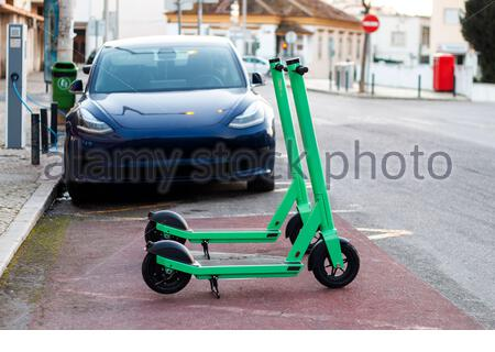Green electric scooters for rent, and charging electric cars parked on the city. - Stock Photo
