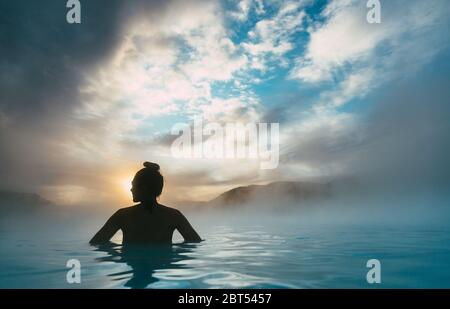 Silhouette of a woman standing in the Blue Lagoon, Iceland - Stock Photo