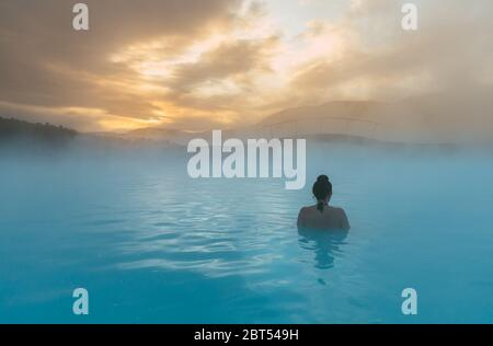 Rear view of a woman standing in the Blue Lagoon, Iceland - Stock Photo
