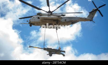 U.S. Marine Corps CH-53E Super Stallion helicopter with Marine Heavy Helicopter Squadron 463 lifts the M777 Howitzer during a hoist lift exercise on Marine Corps Base Hawaii, May 21, 2020. HMH-463 worked with 1st Battalion, 12th Marines and Combat Logistics Battalion 3 to increase proficiency and combat readiness. (U.S. Marine Corps photo by Cpl. Eric Tso) Stock Photo