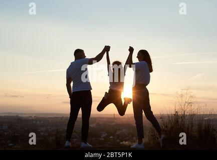 Silhouette of father, mother and daughter having fun outside the city on the hill on the sunset with a beautiful city view, man and woman holding girl by hands and she is jumping, back view - Stock Photo