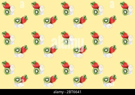 Colorful summer fruit mix pattern of fresh strawberry, kiwi and banana pieces on yellow background. Minimal flat lay food texture.