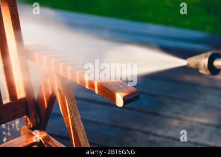 power washing garden furniture - made of exotic wood - very shallow depth of field - Stock Photo