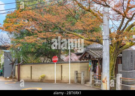 tokyo, japan - march 30 2020: Small shrine dedicated to Jizo bodhisattva symbol of filial piety to protect children and decorated with garlands of tho - Stock Photo