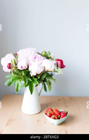 Bunch of Pink peonies in vase and strawberry on the wooden table . Flowers on a beige wooden table near the window. Home house interior. Beautiful