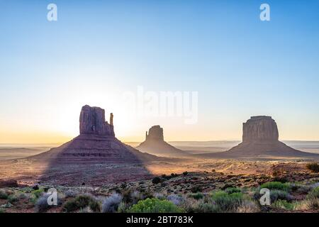 Panoramic view of merrick mitten buttes and horizon in Monument Valley at sunrise colorful light and sun beam rays behind rocks in Arizona - Stock Photo