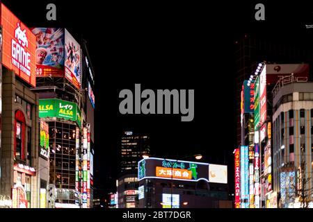 Tokyo, Japan - April 3, 2019: Shinjuku ward downtown near Kabukicho street road with neon colorful illuminated city lights cityscape skyline and adver - Stock Photo