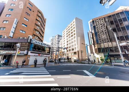 Tokyo, Japan - April 1, 2019: Shinjuku street with people waiting at crosswalk in morning commute on road wide angle view with flare - Stock Photo