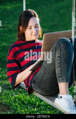 Peaceful happy young woman sitting comfortably on the swings with laptop - Stock Photo