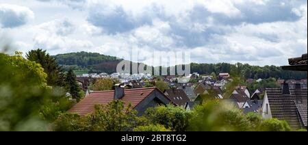 view over a village, rooftops, hills in the background, cloudy sky - Stock Photo