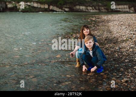 Blond boy in hat and girl playing at river shore. Kids weat rubber boots. Spring activities