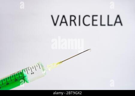 This photo illustration shows a disposable syringe with hypodermic needle, VARICELLA written on a white board behind Stock Photo