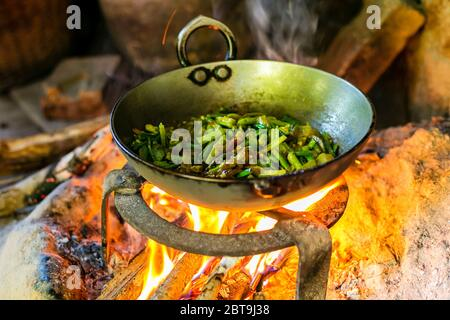 Cooking Vegetable curry in Outdoor Kitchen on Fire Wood in Local Village of Nepal. - Stock Photo