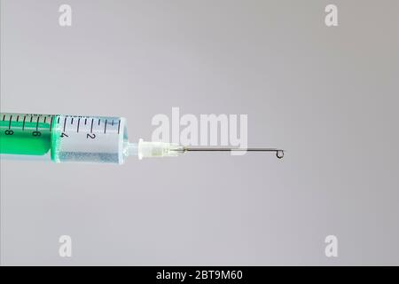 This photo illustration shows a disposable syringe with hypodermic needle, a white board behind Stock Photo