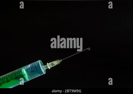 This photo illustration shows a disposable syringe with hypodermic needle, a black board behind Stock Photo