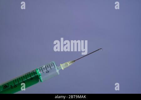 This photo illustration shows a disposable syringe with hypodermic needle, a grey board behind Stock Photo