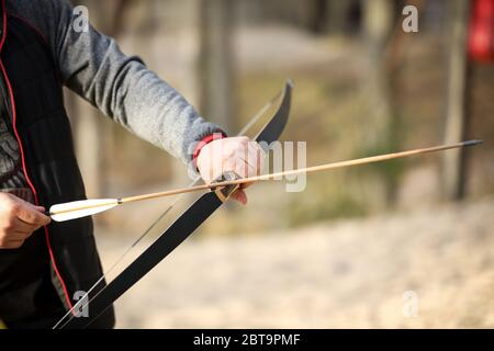 Man holds a bow and aims at the target. Boy shoots a bow in the forest