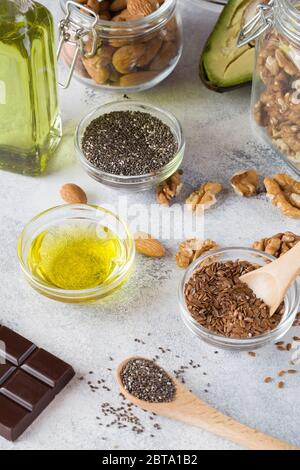 healthy fats sources flax nuts oil avocado chia seeds and bitter chocolate on blue background . healthy food concept, - Stock Photo