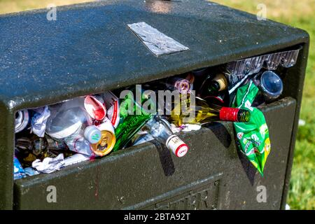 A litter bin in a park overflowing and full of rubbish (Battersea Park, London, UK) - Stock Photo