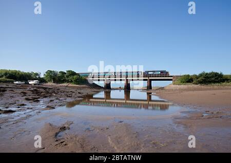 Direct Rail Services class 37 diesel locomotive 37409 crossing the river Mite at Ravenglass, west Cumbria  with a Northern rail train - Stock Photo