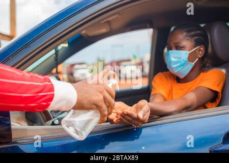 Woman in a car receiving alcohol gel or sanitizer gel for washing hands, corona virus or Covid-19 protection.