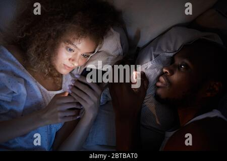 Above view at young mixed-race couple using smartphones while lying in bed at night, focus on smiling curly-haired woman