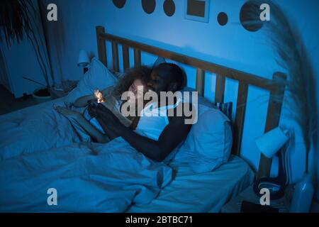 High angle portrait of young mixed-race couple lying in bed at night looking at smartphone screen while talking, copy space