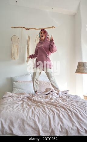 Happy teen girl pink hair wear headphone listening music jumping dancing on bed. - Stock Photo