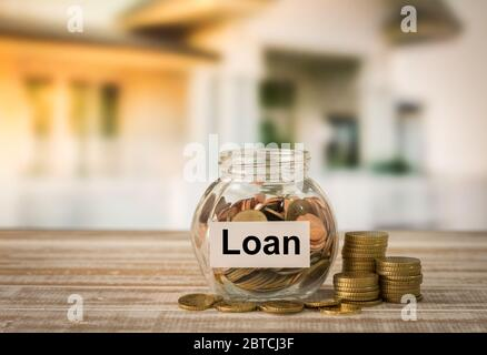 Golden coins in money jar with loan label. Concept of financial planning for housing, home savings, home loans. - Stock Photo