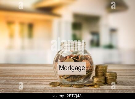 Golden coins in money jar with mortgage label. Concept of financial planning for housing, home savings, home loans. - Stock Photo