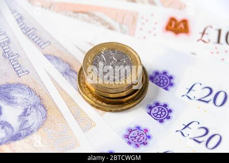 Close up view of one pound coin on polymer currency denomination of ten and twenty in background - Stock Photo