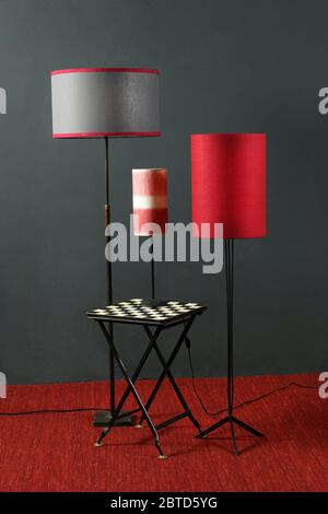 Striking red and black interior decor with vintage floor and table lamps with cylindrical shades against a grey wall in an interior design concept - Stock Photo