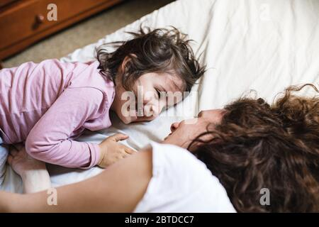 A little girl lying down in her mother's bed laughs while they have a great time playing around
