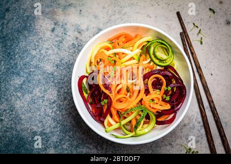 Vegetable noodles - zucchini, beets and carrots in a bowl, dark background. Raw vegan food. - Stock Photo