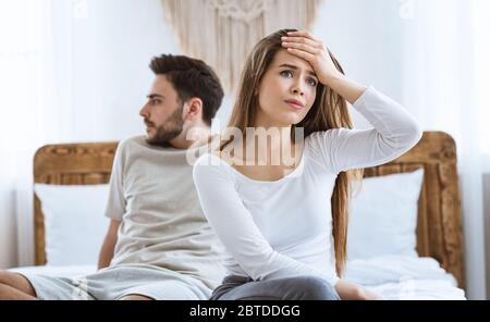 Offended spouses turned away from each other, sitting on bed in bedroom - Stock Photo
