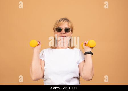 People, age, sports and active lifestyle concept. Picture of happy positive mature retired woman in t-shirt doing exercise with free weights in gym