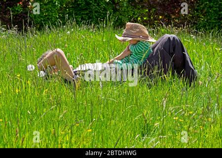 Person grandfather lying in meadow long grass lawn holding baby wearing straw hat in spring May garden Carmarthenshire Wales UK   KATHY DEWITT - Stock Photo