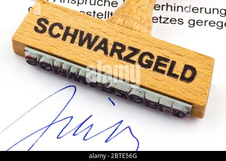 wooden stamp on a document lettering Schwarzgeld, black money - Stock Photo