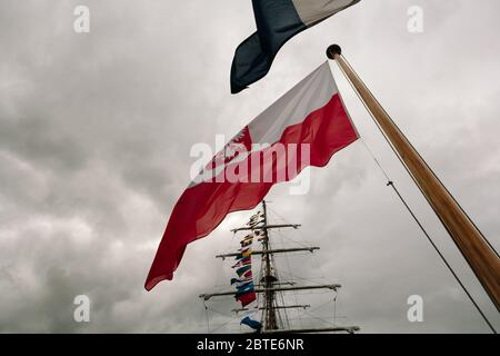 The Polish flag flying on the square-rigged Polish training ship Dar Mlodziezy during the Tall Ships Race in Greenock, Scotland. - Stock Photo