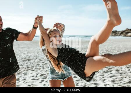 Parents swinging daughter up into air on the beach. Happy family being playful while taking a walk on the beach - Stock Photo