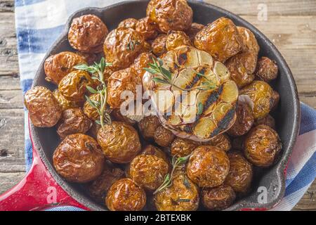Baked in frying pan whole young potatoes, homemade bbq vegetarian food - Stock Photo